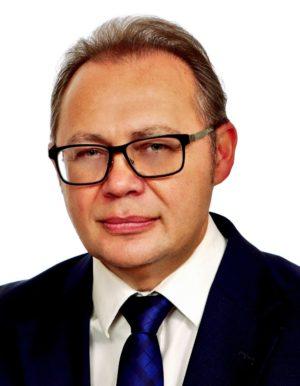 Wojciech Kędzia, mężczyzna w okularach, białej koszuli i czarnej marynarce.