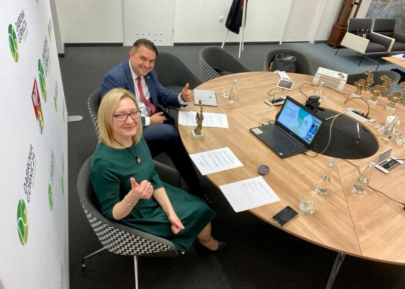 Kobieta i mężczyzna przy okrąglym stole, na nim laptop i kartki. Osoby podnoszą w górę kciuk.