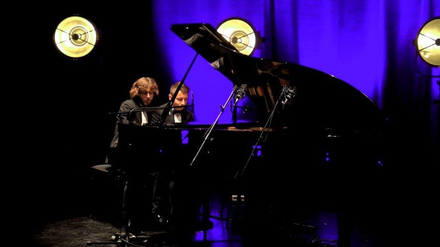Dwóch mężczyzn w garniturach grających na fortepianie.
