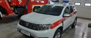 Biały samochód strażacki marki Dacia Duster z czerwonym pasem.